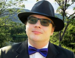 Picture of James P. Morgan - Caucasian Male, Thirties, Clean Shaven, Black Suit, Glasses, and Classic Fedora, Backdrop of sunny green landscape with trees river and sky.